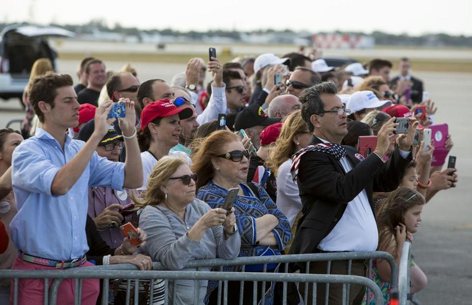 Supporters in a crowd watch as President Donald Trump aboard Air Force One arrives at the Palm Beach International Airport, Thursday, April 13, 2017, in West Palm Beach, Fla. (Richard Graulich/Palm Beach Post via AP)