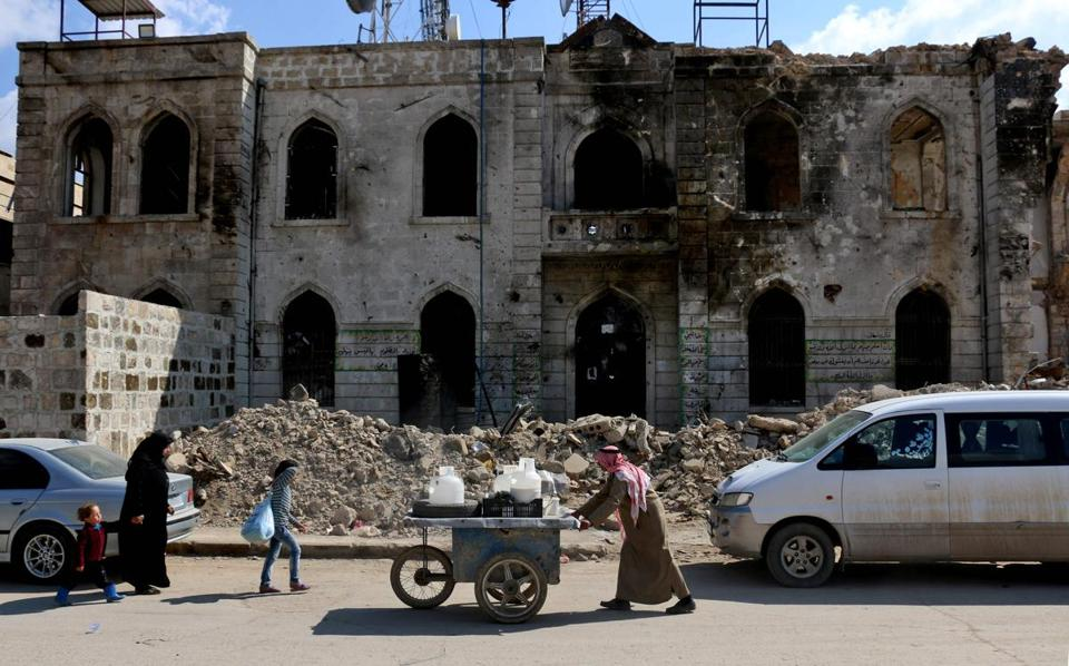 A peddler pushed his cart past a damaged courthouse in Azaz, on Syria's Turkish border.
