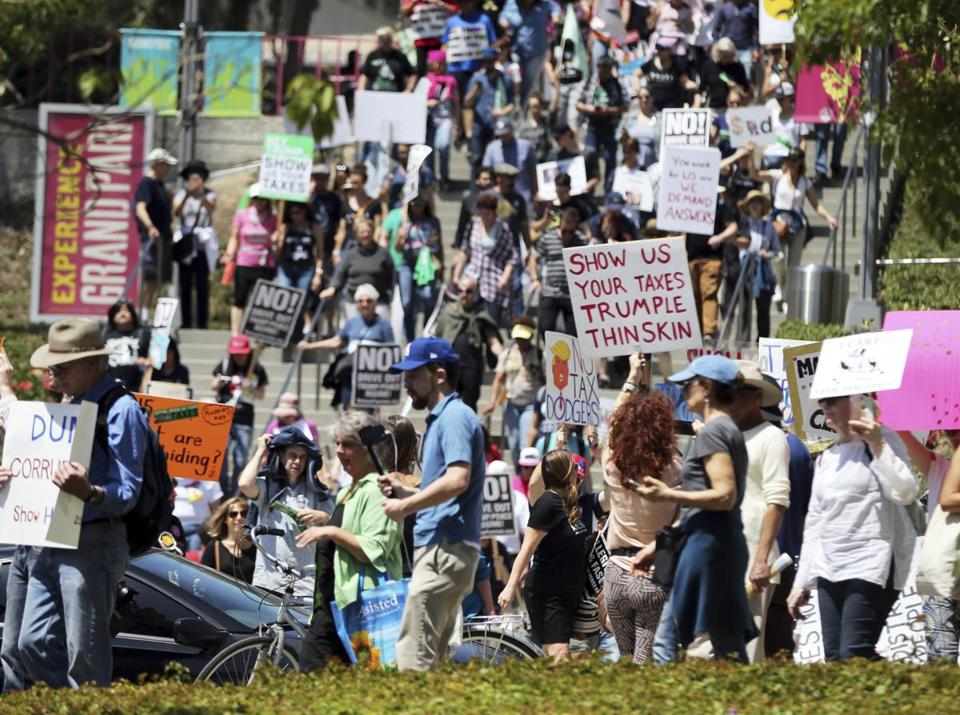 Demonstrators protest President Donald Trump's failure to release his tax returns and a host of other issues during a march and rally in downtown Los Angeles Saturday, April 15, 2017. (AP Photo/Reed Saxon)