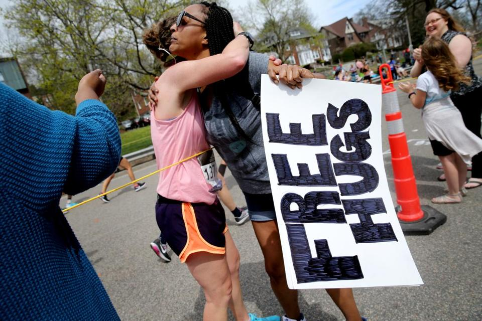 Candice Woodson of Dorchester offered hugs to runners after they finished Heartbreak Hill.