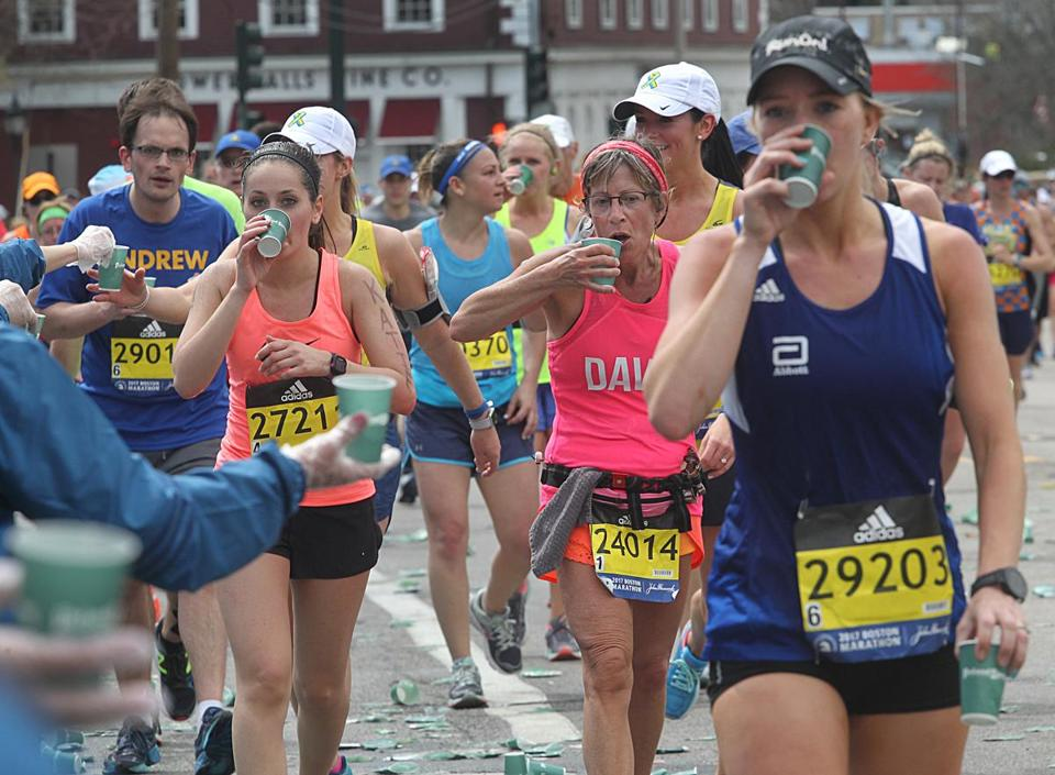 Newton, MA., 04/17/17, The heat is up and the water stations are busy during the 121st running of the Boston Marathon. Globe staff/Suzanne Kreiter