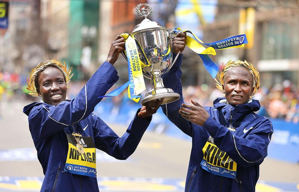 Elite winners Edna Kiplagat, left, and Geoffrey Kirui hold the trophy at the finish line.