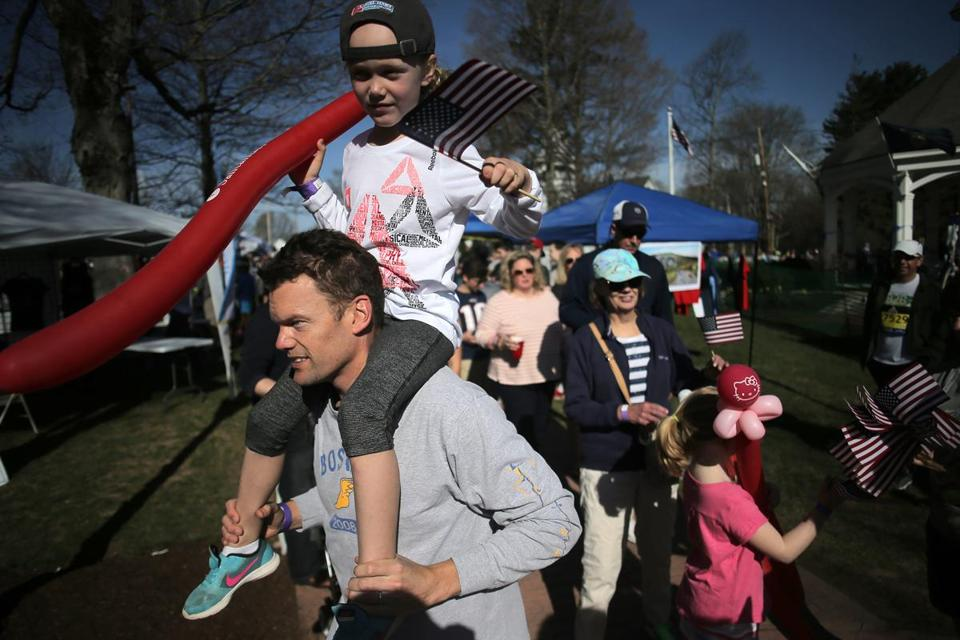 Matt Colleran and his daughter Riley of Hopkinton make their way through the start village in Hopkinton.
