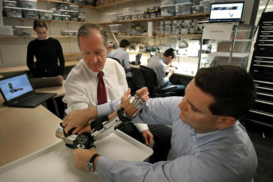 Myomo VP Gene Tacy checked a device on the arm of CEO Paul Gudonis.