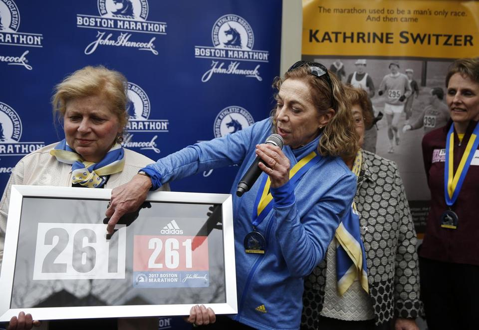 Kathrine Switzer, right, points to her bib number being held by BAA President Joann Flaminio as she thanks the crowd during a ceremony to have her bib number, 261, retired.