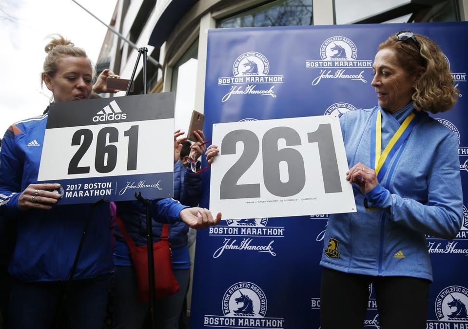 Kathrine Switzer, right, holds a reproduction of her original bib number, 261, during a ceremony to have her bib number retired.