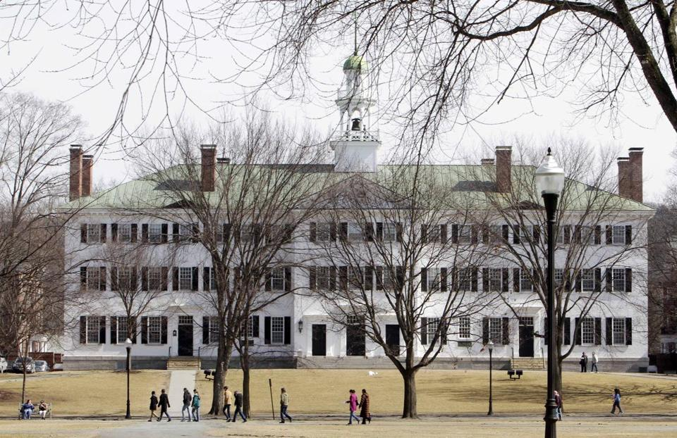 Students walk across the Dartmouth College campus green.