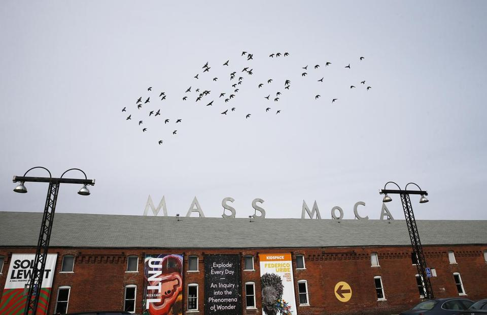 North Adams, MA -- 3/13/2017 - Birds fly over a sign near the entrance of MASS MoCA. MASS MoCA is preparing to open Building 6, a 130,000 square foot expansion that will make it the largest contemporary art museum in the country. (Jessica Rinaldi/Globe Staff) Topic: MassMoCA Reporter: Malcolm Gay