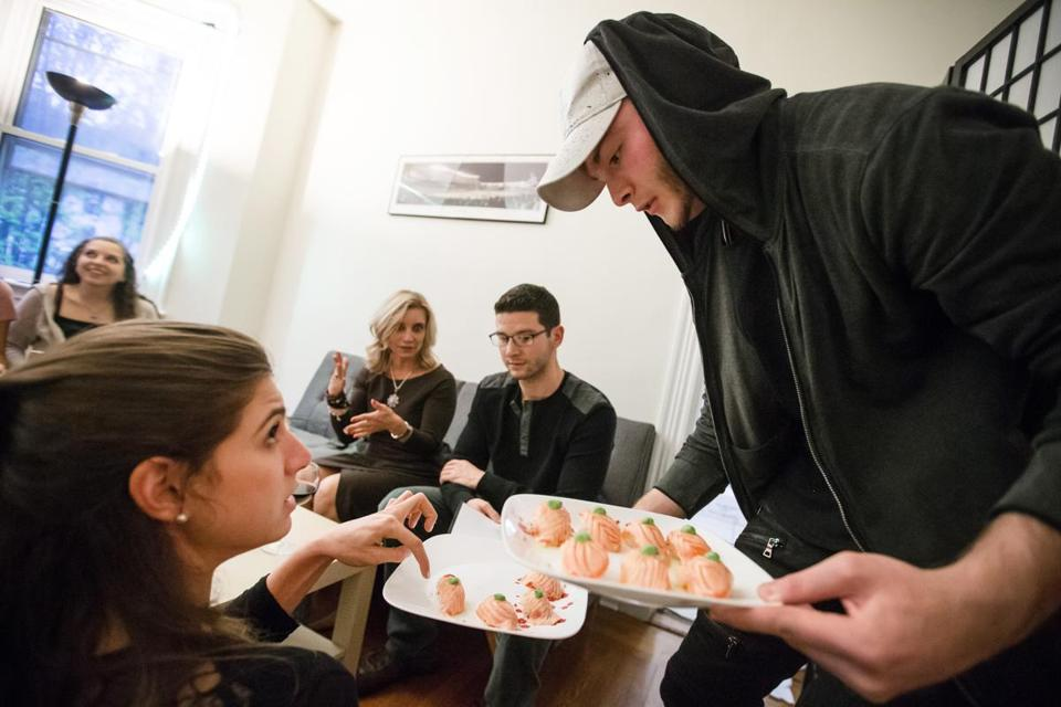 05/05/2017 BROOKLINE, MA Jarrett Deutsch, 19, (right) serves Melissa Solomon (cq) during a pop up sushi dinner held at a townhouse in Brookline by BU students Ethan Cole (cq) 19, and Jarrett Deutsch, 19. (Aram Boghosian for The Boston Globe)