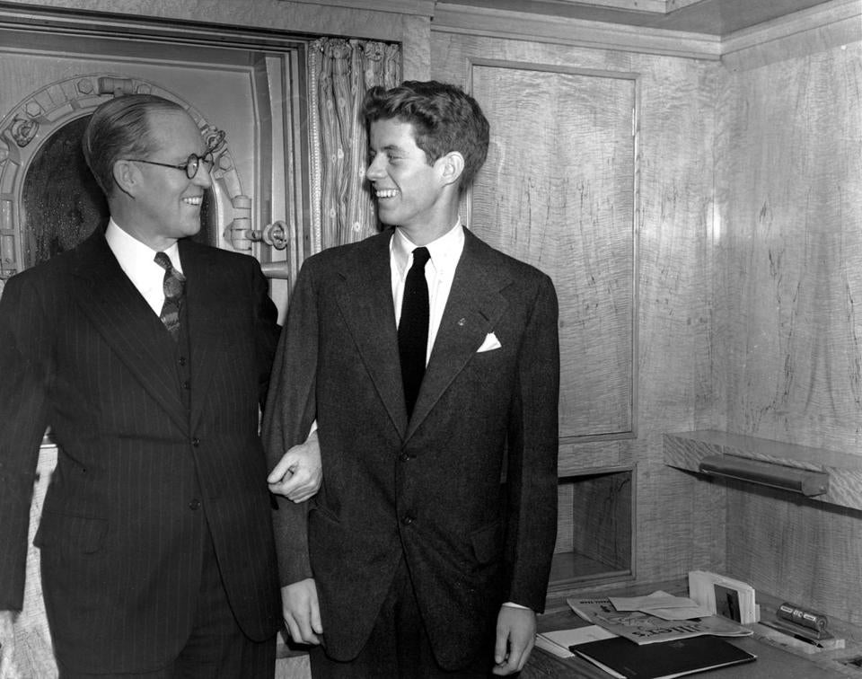 FILE - In this Jan. 5, 1938 file photo, Joseph P. Kennedy, left, U.S. Ambassador to Great Britain, stands with his son, John F. Kennedy, in New York. The voice of a young John F. Kennedy can be heard on what Harvard University believes is the earliest known recording of the late president. The school says the recording was restored by a Harvard archivist from a 1937 aluminum disk recording made by Kennedy's professor in a public speaking course.(AP Photo, File)