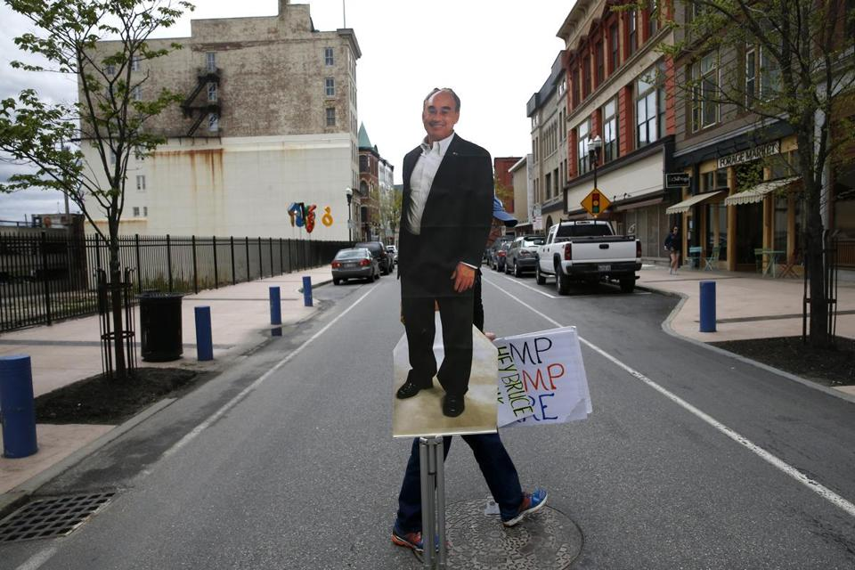 Bill Trommer, of Leeds, Maine, carried a poster of Representative Bruce Poliquin at the end of a protest held outside of his office.