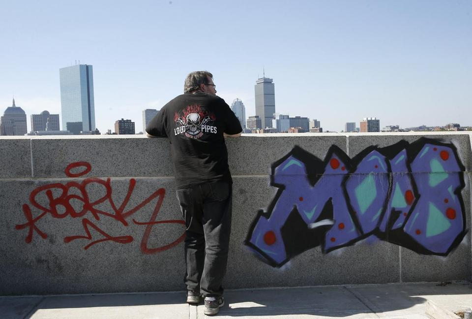 A man paused to look at the skyline next to graffiti scrawled on the Longfellow Bridge in Boston.