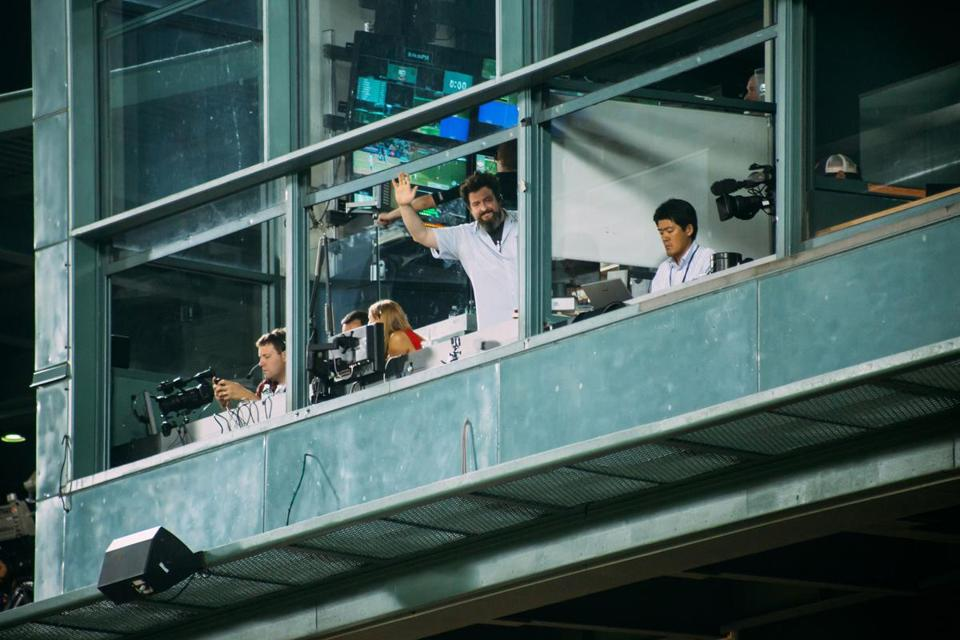 TJ Connelly waves from his booth at Fenway Park.