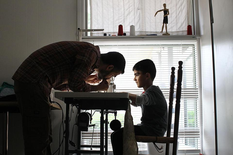 Framingham, Ma., 05/07/17, Nine year old Mustafa Hayani is the same age his father, Adbulkader ,had been when he left school in Syria for good to start working as a tailor. Abdulkader helps Mustafa with a piece of sewing in the room in their house that doubles as a play room and a sewing room. Globe staff/Suzanne Kreiter