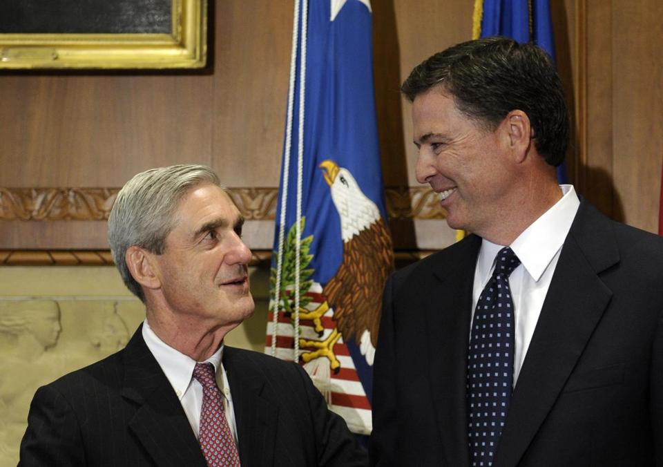 Incoming FBI Director James Comey talks with outgoing FBI Director Robert Mueller before Comey was officially sworn in at the Justice Department in Washington, Wednesday, Sept. 4, 2013. (Susan Walsh/AP Photo)