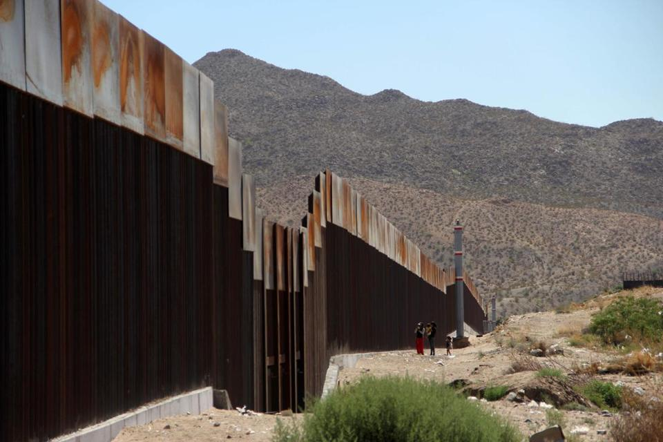 A Mexican family stood next to the border wall between Mexico and the United States, in Ciudad Juarez, Mexico, on Tuesday.
