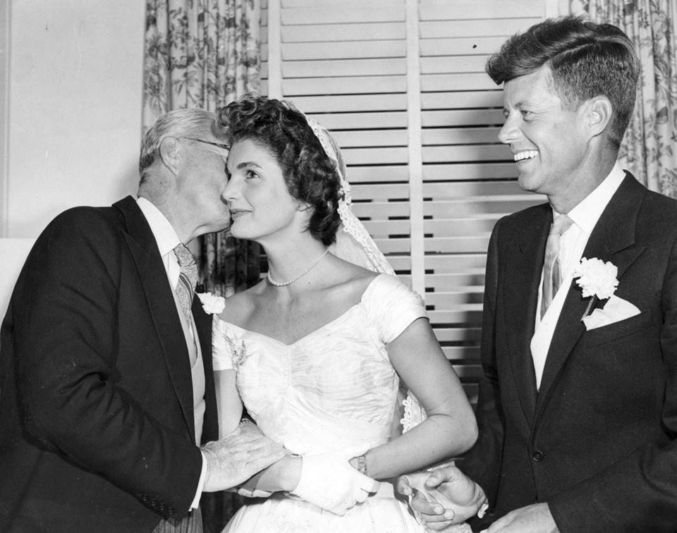 Newport, RI - 9/12/1953: Senator John F. Kennedy, right, smiles as his father, Joseph P. Kennedy Sr., left, kisses bride Jacqueline Kennedy at the couple's wedding reception in Newport, R.I. on Sept. 12, 1953. (Charles McCormack/Globe Staff) --- BGPA Reference: 150323_MJ_003 jfk100