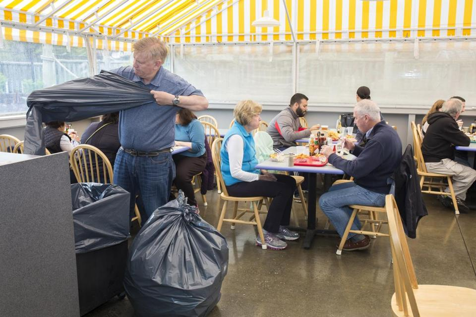 "Nathan ""Nick"" Nickerson, the owner of Arnold's, a restaurant, clam shack, and mini golf place in Eastham, switchef out trash bags during Friday's busy lunch hour before Memorial Day Weekend."