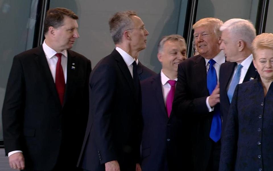 In this image taken from NATO TV, Montenegro Prime Minister Dusko Markovic, second right, appears to be pushed by President Donald Trump as they were given a tour of NATO's new headquarters.