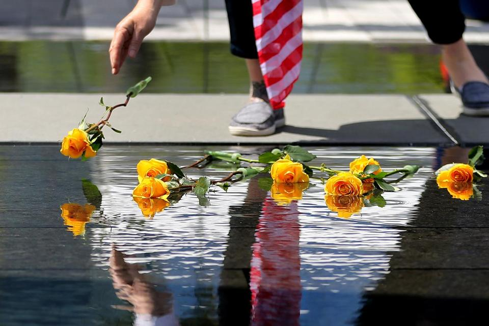 A Gold Star family member placed a yellow rose into the water of the Massachusetts Fallen Heroes Memorial during a re-dedication ceremony on Saturday.