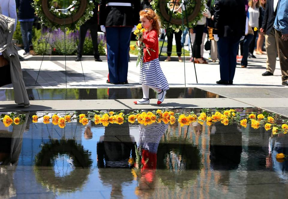 Brooklynn Eggers, 4 from Londonderry, N.H., carried yellow roses to place into the water of the Massachusetts Fallen Heroes Memorial during a re-dedication ceremony held at the site on Northern Avenue.