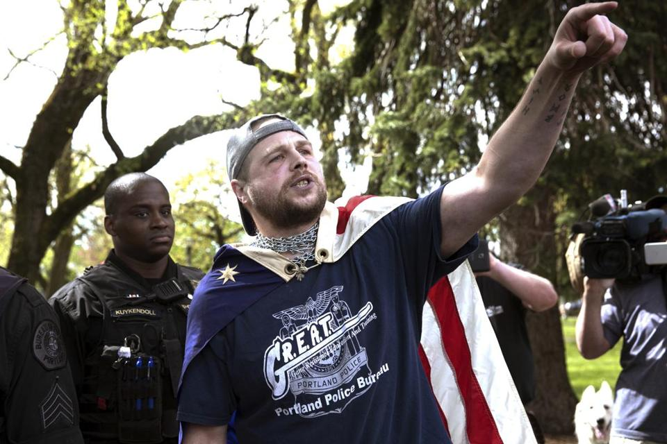 In an April 29 photo, Jeremy Joseph Christian (right) was seen during a Patriot Prayer organized by a pro-Trump group in Portland, Ore.