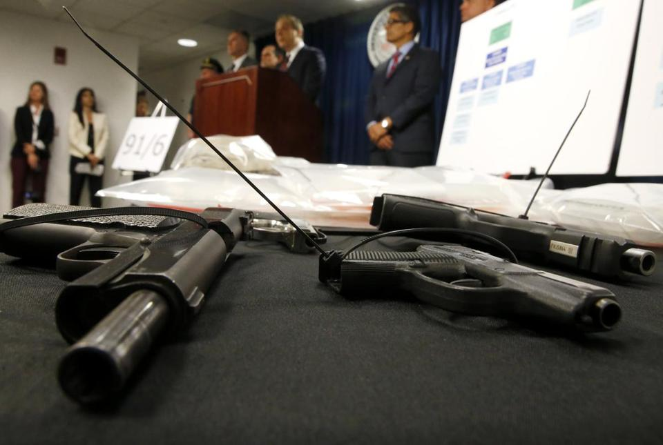 Boston, MA -- 5/30/2017 - Confiscated firearms are seen in the foreground as Acting United States Attorney William D. Weinreb announces federal drug, firearm and immigration charges against 30 defendants from the city of Lawrence and surrounding communities at Moakley Federal Courthouse. (Jessica Rinaldi/Globe Staff) Topic: 31lawrencepic Reporter: