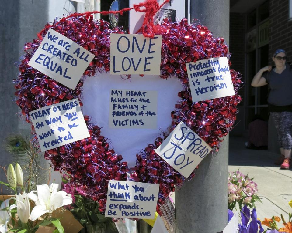 A heart-shaped wreath covered with positive messages hung on a traffic light pole at a memorial for two bystanders who were stabbed to death Friday while trying to stop a man who was yelling anti-Muslim slurs.