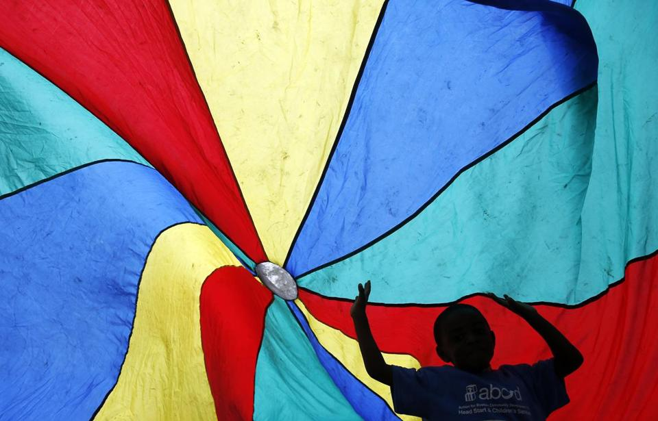 Boston, Massachusetts -- 6/9/2015-- A child from the Hyde Park Head Start program is silhouetted as he plays underneath a parachute during a celebration of 50 years of the Head Start program on the Boston Common in Boston, Massachusetts June 9, 2015. Jessica Rinaldi/Globe Staff Topic: 10abcd Reporter: