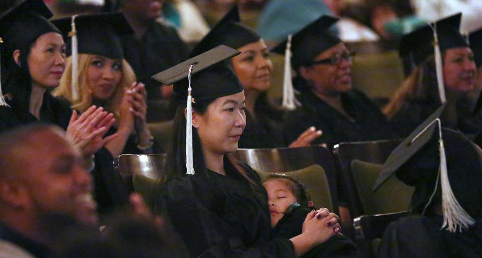 Boston, MA - 6/4/2017 - Mei Feng Zhong's 4-year-old daughter Katherine Fang (cq) naps on her lap during part of the ceremony. Zhong earned a Certificate of Achievement in Early Childhood Education. The Urban College of Boston (cq) holds its Twenty-second Annual Commencement at The Cutler Majestic Theatre. Photo by Pat Greenhouse/Globe Staff Topic: 05urbangrads Reporter: XXX