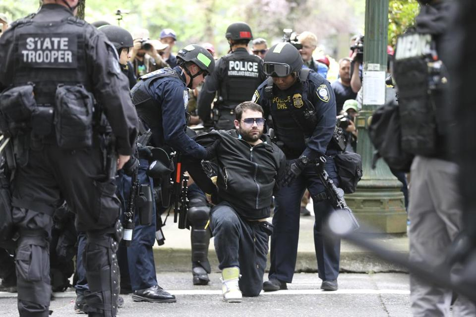 A protester was detained by Portland, Ore., police on Sunday during a demonstration
