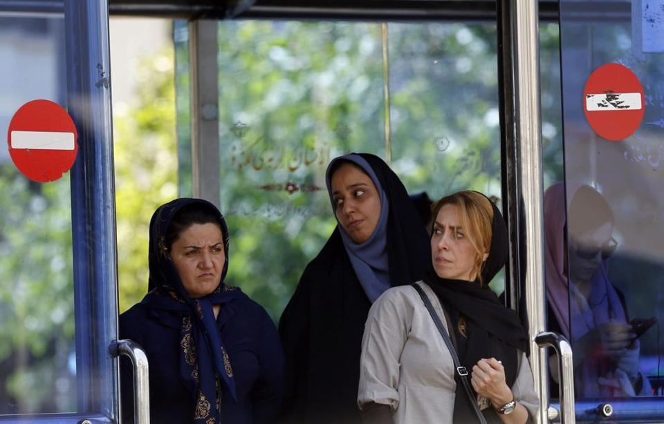 Women waited for a bus in Tehran on Thursday. Iran said that the five men who killed 17 people in the attacks were Islamic State group members.