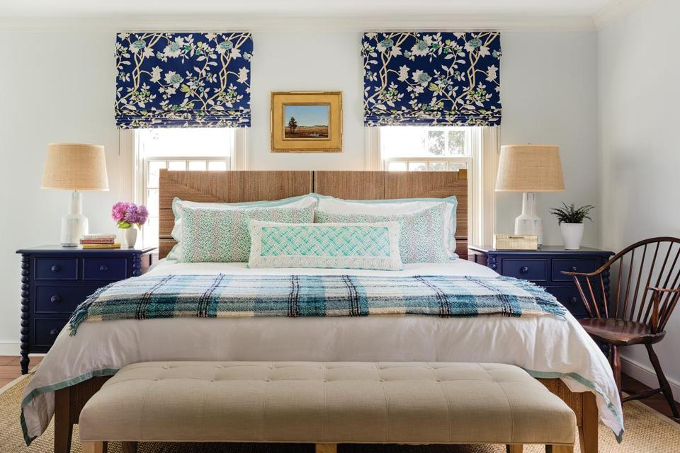 The king-size master bed is from Serena & Lily. Navy blue night stands with turned legs were custom made to pair with the Roman shades in a blue floral Quadrille fabric. The 12-over-12 paned windows emulate a style found in Colonial-era residences.