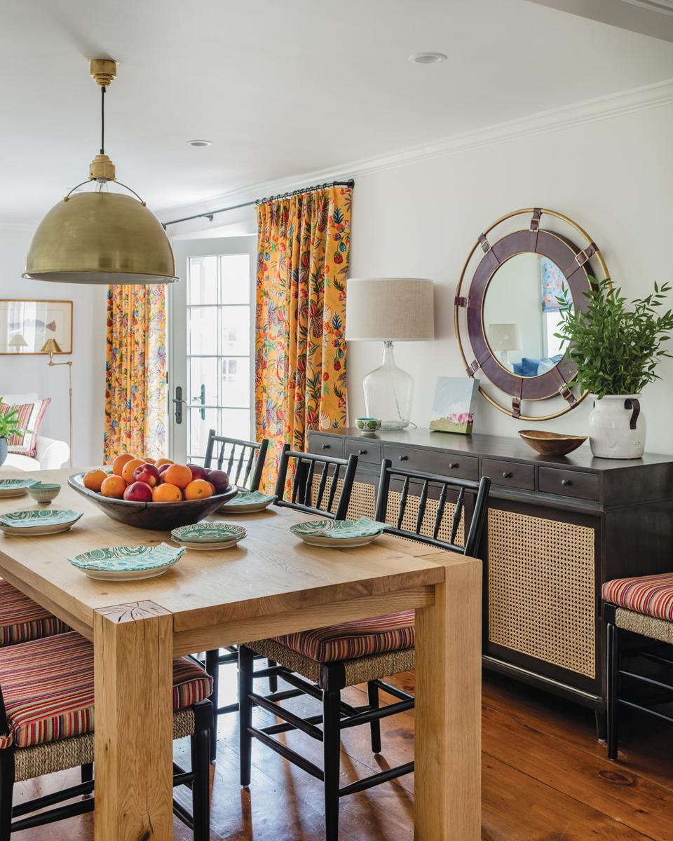 "In the dining area, the Crate & Barrel ""Big Sur"" table accommodates a crowd for both casual dining and large holiday gatherings; the extended family celebrated last Christmas on the Cape. Black chairs with lively seat cushions are from Noir; the brass pendant is by Visual Comfort."