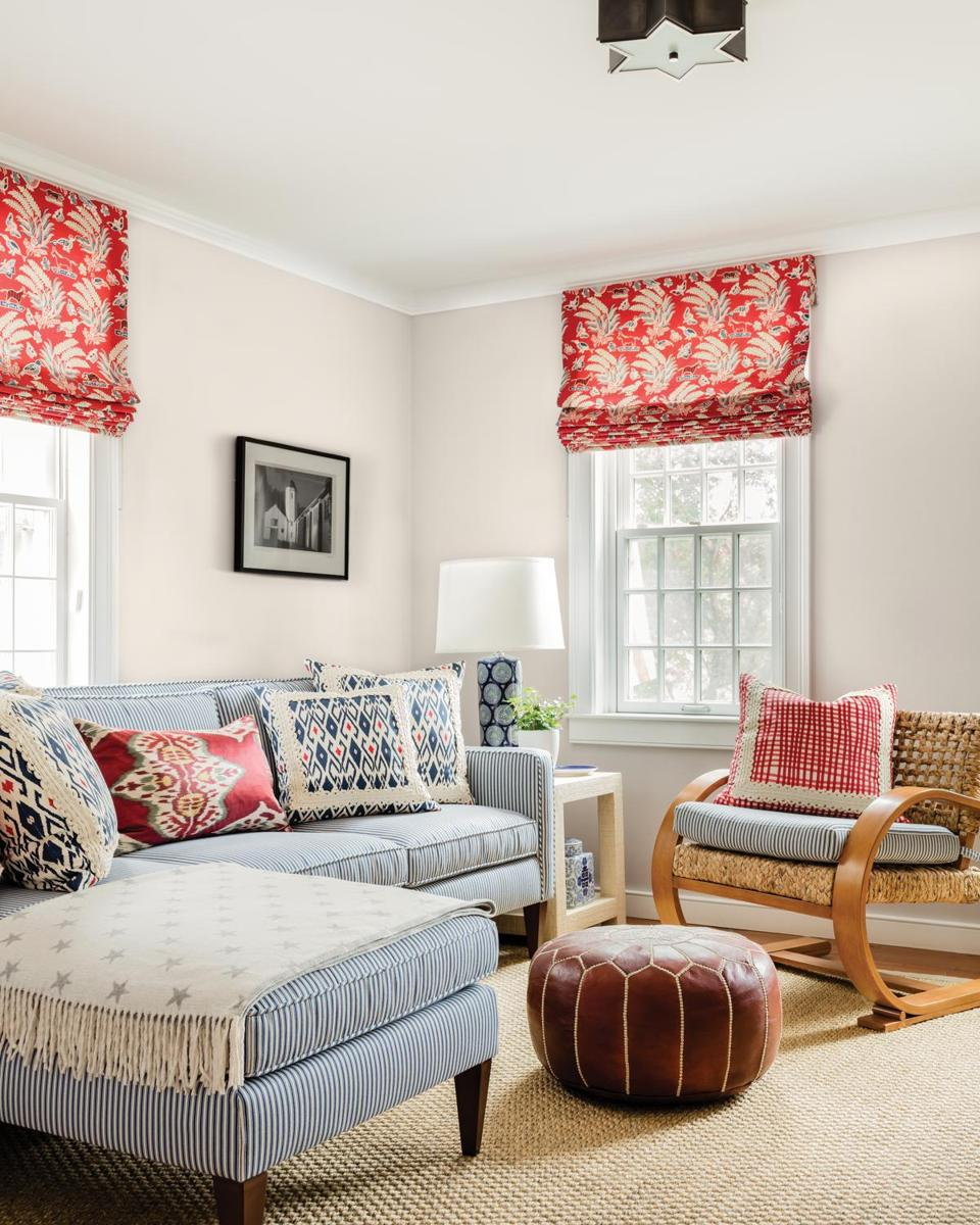 In a sitting room off the main living area, a subtle red-white-and-blue theme reigns. Designer Katie Rosenfeld searched for a sectional that would fit in the compact room; the Crate & Barrel piece was custom upholstered in a blue-and-white pinstripe. The same fabric covers the seat cushion on the woven Wisteria chair. The red print fabric in the Roman shades is from Quadrille. All of the table lamps in the home are by Jamie Young.