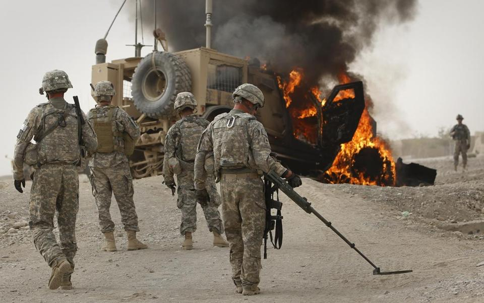 A member of the US Army's explosive ordinance disposal (EOD) unit scans the area around a burning M-ATV armored vehicle after it struck an improvised explosive device (IED) near Combat Outpost Nolen in the Arghandab Valley north of Kandahar July 23, 2010. REUTERS/Bob Strong (AFGHANISTAN - Tags: CONFLICT MILITARY) Library Tag 07242010 National/Foreign
