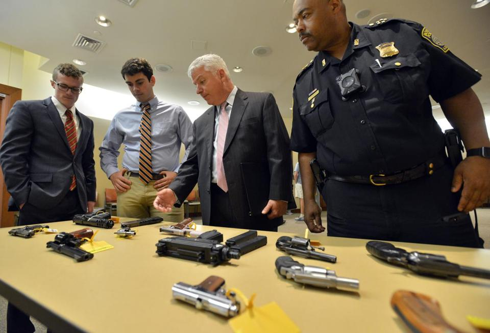 Suffolk County District Attorney Daniel Conley center, and Chief William Gross right, discuss some of the guns seized recently following a press conference to announce the end of a year-long investigation, which resulted in indict seventeen individuals and the seizure of 22 firearms. Josh Reynolds for The Boston Globe (Metro, Schworm )