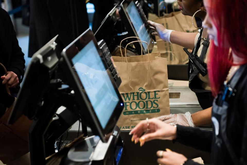 Employees ring up customers at the checkout counter of a Whole Foods Market.