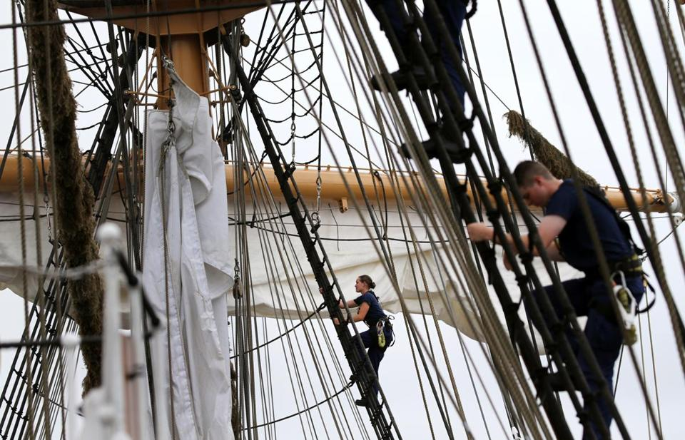 Cadets climb the rigging Saturday while dousing the sails aboard the USCGC Eagle during the Grand Parade of Sail in Boston.