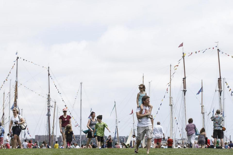 Boston, MA - 6/18/2017 - Crowds of visitors walk along the Public Green near Fan Pier in front of tall ships that are taking part of the Sail Boston event on Fan Pier in Boston, MA, June 18, 2017. (Keith Bedford/Globe Staff)
