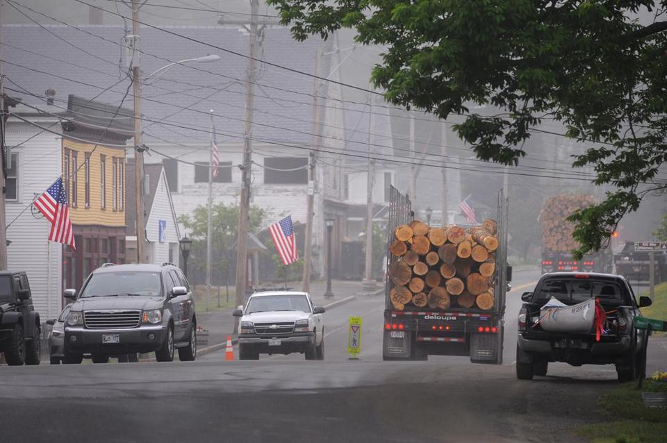 Lumber trucks passed through early morning fog in downtown Monson.