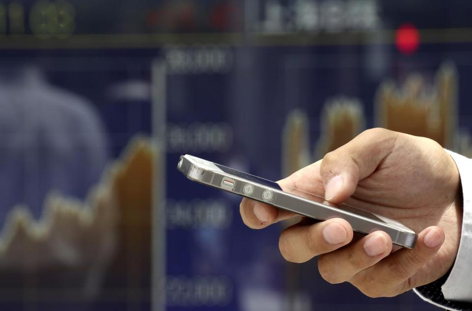 A man uses a smartphone in front of an electronic stock indicator of a securities firm in Tokyo, Thursday, June 22, 2017. Asian financial markets were mostly higher after a plunge in oil prices dragged down energy stocks on Wall Street. (AP Photo/Shizuo Kambayashi)