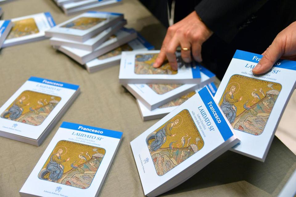 "People held copies of ""Laudato Si"" in 2015, during its official unveiling at the Vatican."