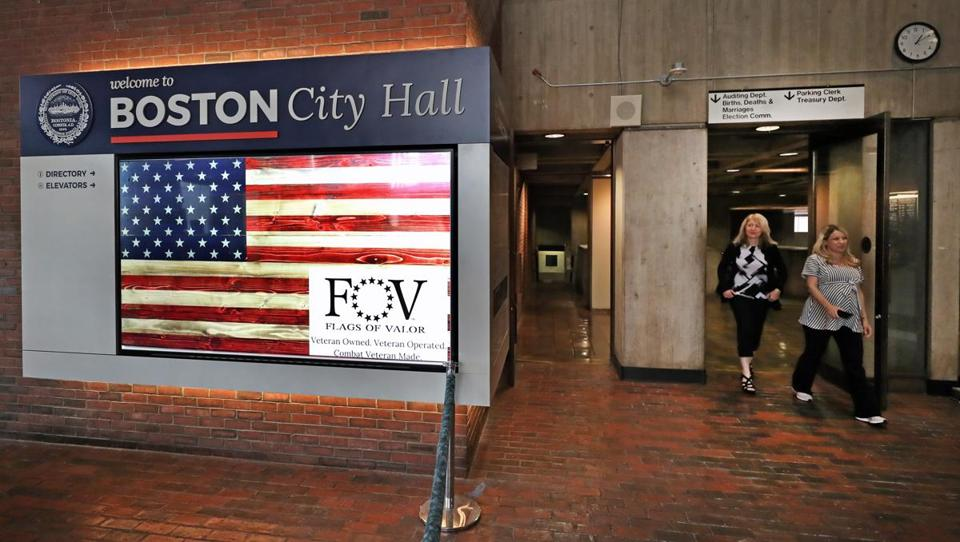 BOSTON, MA - 6/29/2017:A video screen on the left. Improvements to City Hall Plaza, during weekdays local workers from throughout downtown gather for lunch on Adirondack chairs, or picnic tables, or stop to toss a beanbag on artificial turf laid over red brick. Inside City Hall, the city spent millions to renovate the mezzanine, where advocacy groups can stage events. a coffee shop and there is an installed signage video screens promoting city programs. (David L Ryan/Globe Staff ) SECTION: METRO TOPIC 28cityhall