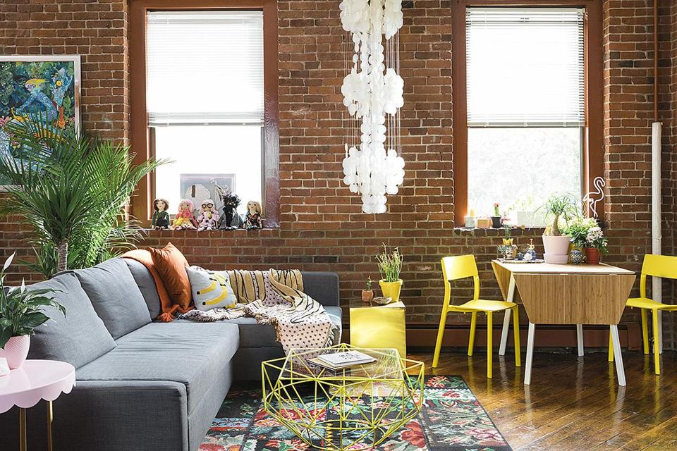 She scored the '70s shell lamp at an antiques fair in Rhode Island. The sofa and carpet are from IKEA and the side tables from Target; Robertson spray-painted the base of the West Elm coffee table yellow.