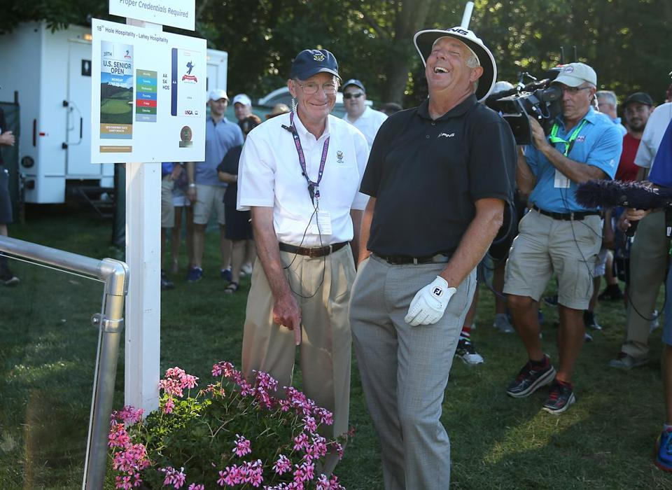 Kirk Triplett (right) shares a laugh with a marshal after he pointed out that his ball was in the flower planter on the 18th hole during the final round of the US Senior Open Championship.