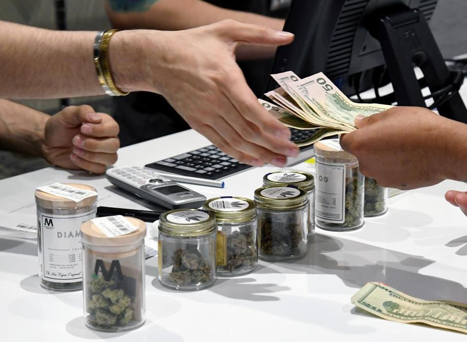 LAS VEGAS, NV - JULY 01: A customer pays for cannabis products at Essence Vegas Cannabis Dispensary after the start of recreational marijuana sales began on July 1, 2017 in Las Vegas, Nevada. Nevada joins seven other states allowing recreational marijuana use and becomes the first of four states that voted to legalize recreational sales in November's election to allow dispensaries to sell cannabis for recreational use to anyone over 21. (Photo by Ethan Miller/Getty Images)