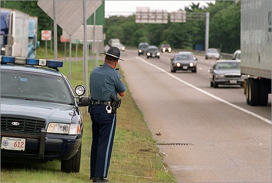 A state trooper used a radar gun to monitor vehicle speeds on Route 128 this summer.