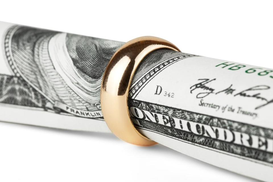 One hundred dollar bill in a gold wedding ring