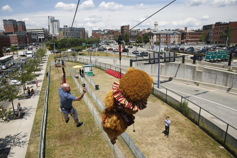 Boston, MA -- 7/10/2017 - Ernesto Galan (L) films Boston Ballet's The Nutcracker Bear as it rides The Z - Boston's Zipline on the Rose Kennedy Greenway. The Ballet was promoting The Nutcracker whose tickets go on sale today. (Jessica Rinaldi/Globe Staff) Topic: Reporter:
